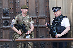 © Licensed to London News Pictures. 27/05/2017. LONDON, UK.  Armed soldiers provide additional security with police officers outside the Houses of Parliament in Westminster today following the risk of a terrorist attack on the capital.  Photo credit: Vickie Flores/LNP