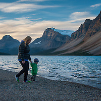 A mother and her son walk beside Bow Lake in Banff National Park, Alberta, Canada.  Bow Crow peak and Crowfoot Mountain are in the background.