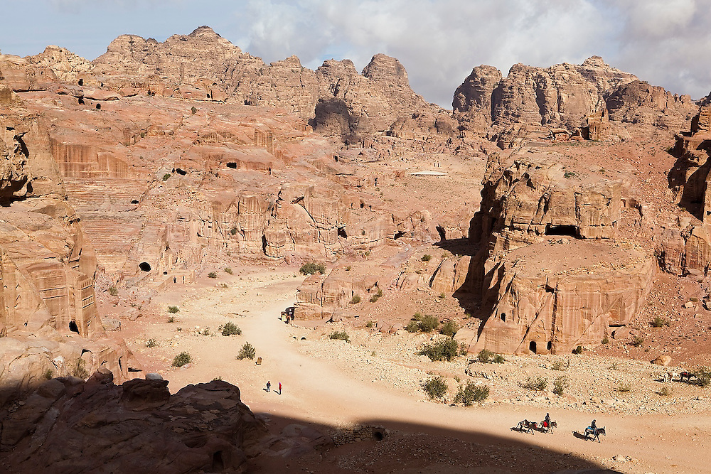 Horsemen and tourists among the tombs of the Street of Facades in Petra, Jordan.