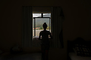An inhabitant of Bento Rodrigues, a district of the city of Mariana in brazilian state of Minas Gerais, looks through the window of a hotel where is housing displaced people because of a mining waste dam failure. On november 5th, a mining waste dam failed causing a flood of mud.