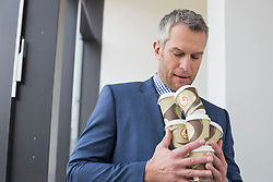 Businessman holding coffee cups to go for all