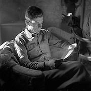 """Al Mozell reading in an Austrian home, May 1945. A patch on his shoulder says Official U.S. War Photographer."""""""