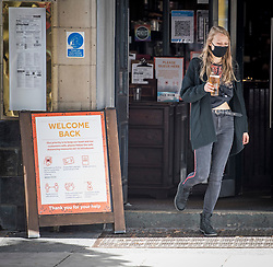 "© Licensed to London News Pictures. 24/09/2020. London, UK. A woman wearing a face mask carries a beer past a sign reading ""WELCOME BACK"" at a pub in Camden, North London, on the first day that pubs will be forced to close at 10pm in an attempt to prevent the spread of COVID-19. Chancellor Rishi Sunak today outlined a series of financial packages to help business through new lockdown measures. Photo credit: Ben Cawthra/LNP"