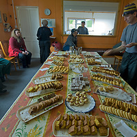 Ship-bourn tourists enjoy cookies and tea in the home of a resident of Carcass Island in Britain's  Falkland Islands.