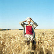 Young woman standing in a wheat field drinking from a bowl.