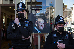Thames Valley Police officers stand alongside an image of the Duke of Edinburgh in a shop window on the day of his funeral on 17th April 2021 in Windsor, United Kingdom. The funeral of Prince Philip, Queen Elizabeth II's husband, is taking place at St George's Chapel in Windsor Castle, with the ceremony restricted to 30 mourners in accordance with current coronavirus restrictions.