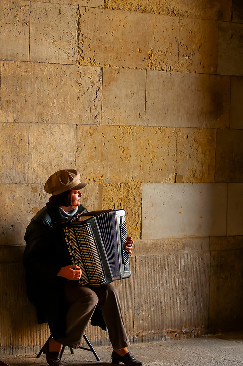 Woman playing accordion in arcade between Theaterplatz and the Zwinger, Dresden, Saxony, Germany