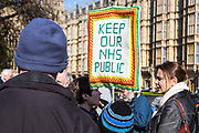 """Protesters outside the British Houses of Parliament holding a placard saying """"Keep Our NHS Public"""".  They are demonstrating against the government section 75 privatization regulations which they believe will force the National Health Service into privatization."""
