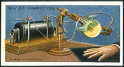 X-ray apparatus powered by a Ruhmkorff coil being used to take an X-ray of a hand. Card published 1915. Chromolithograph