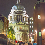 People walking at night under the iconic dome of St Paul's Cathedral in London, England.