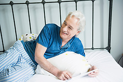 Mature man sitting with digital tablet in bed, smiling