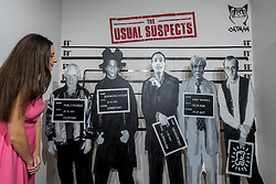 "© Licensed to London News Pictures. 04/10/2018. LONDON, UK. A staff member views ""The Usual Suspects"" by Catman, an artwork comprising mugshots of major contemporary artists.  Preview of Moniker Art Fair, taking place during Frieze Week at the Old Truman Brewery, near Brick Lane.  Now in its tenth year, the fair embraces contemporary urban art from emerging and established artists  This year, the show's theme is 'Uncensored', shedding light on social, economic and ecological issues, and is open 4 to 7 October.  Photo credit: Stephen Chung/LNP"