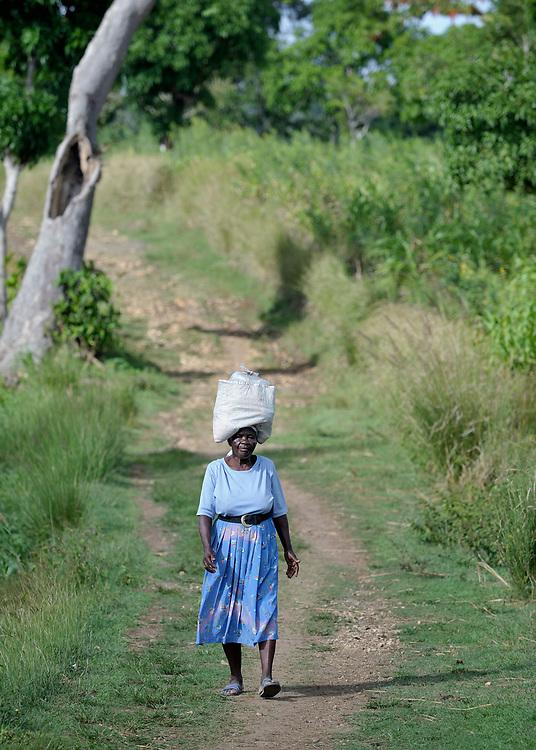 A woman walks along a path in the Haitian village of Mizak.