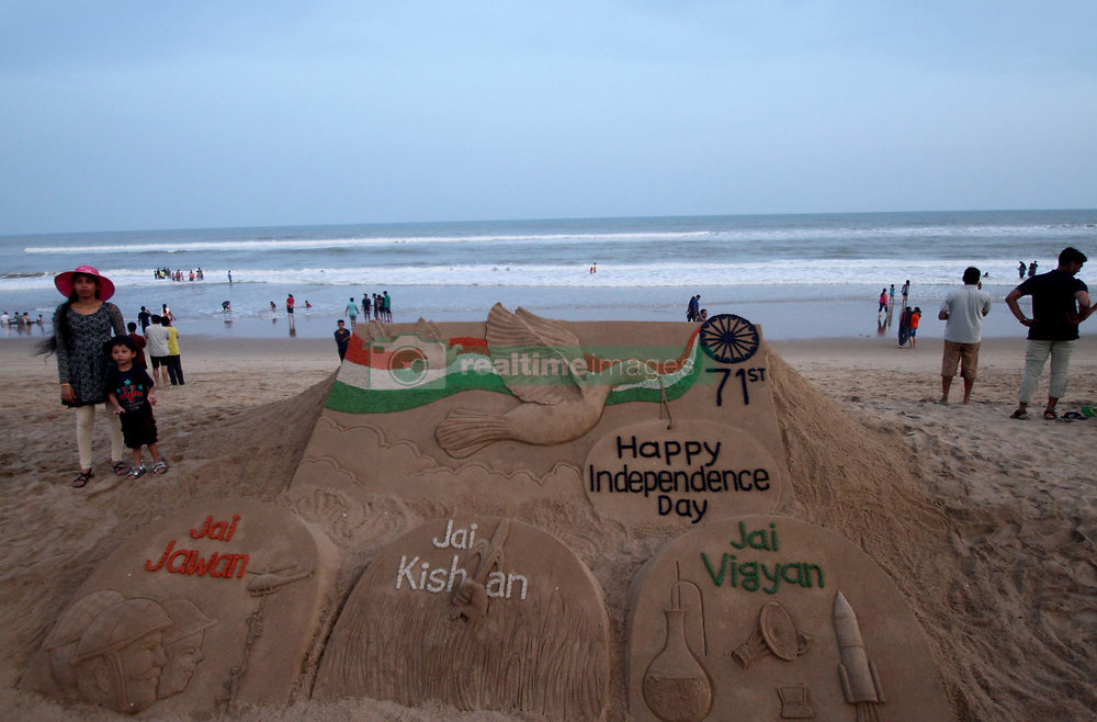 August 14, 2017 - Puri, Bhubaneswar, India - Visitors look near to the Independence Day sand sculpture, creating by sand artist Sudarshan Patnaik at the Bay of Bengal Sea's eastern coast beach at Puri, 65 km away from the eastern Indian state Odisha's capital city Bhubaneswar on 15 August 2017. (Credit Image: © Str/NurPhoto via ZUMA Press)