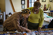 Shady Side, Maryland, US - 21 September 2009. Joan Gaither, left, and a volunteer work on a quilt pieced from memorabilia of black watermen at the Salem Avery Museum in Shady Side, Maryland.