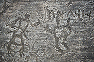 Prehistoric Petroglyph, rock carving, of two schematic human figures with Norhtern Etruscan letters carved by the Camunni people in the ,iddle to late iron age between  900-1200 BC, Rock no 18, Seradina II area , Seradina-Bedolina Archaeological Park, Valle Comenica, Lombardy, Italy .<br /> <br /> Visit our PREHISTORY PHOTO COLLECTIONS for more   photos  to download or buy as prints https://funkystock.photoshelter.com/gallery-collection/Prehistoric-Neolithic-Sites-Art-Artefacts-Pictures-Photos/C0000tfxw63zrUT4<br /> If you prefer to buy from our ALAMY PHOTO LIBRARY  Collection visit : https://www.alamy.com/portfolio/paul-williams-funkystock/valcamonica-rock-art.html