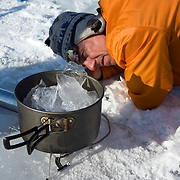 Arkady cooking ice to make tea on the second day trek across frozen Lake Baikal in Siberia, Russia. .They are a group of five people: Justin Jin (Chinese-British), Heleen van Geest (Dutch), Nastya and Misha Martynov (Russian) and their Russian guide Arkady. .They pulled their sledges 80 km across the world's deepest lake, taking a break on Olkhon Island. They slept two nights on the ice in -15c. .Baikal, the world's largest lake by volume, contains one-fifth of the earth's fresh water and plunges to a depth of 1,637 metres..The lake is frozen from November to April, allowing people to cross by cars and lorries.