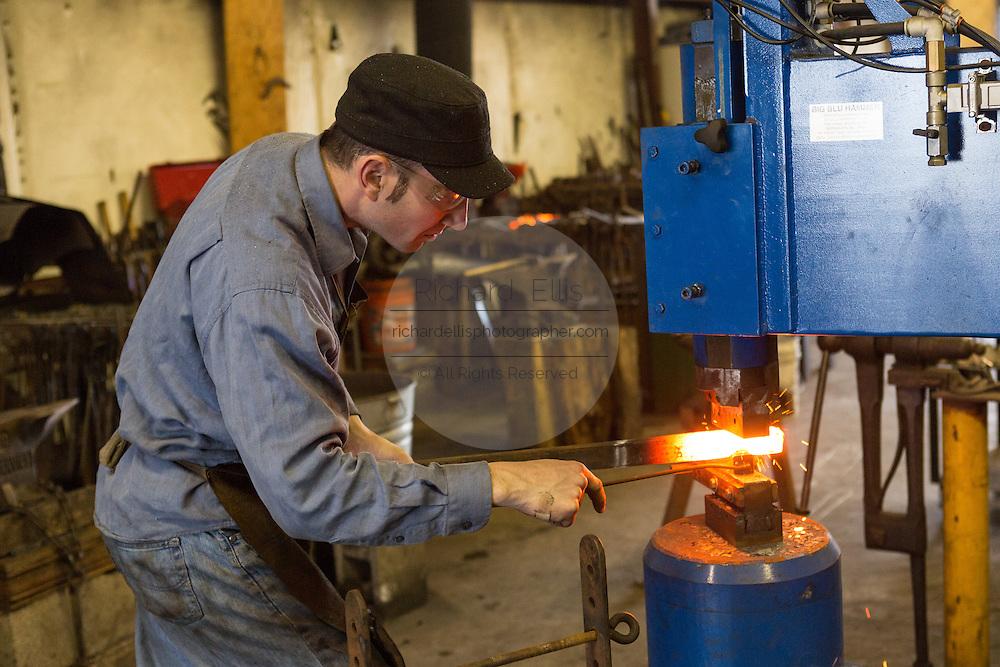 Blacksmith Frank Verga working at a forging hammer in an iron working shop in Charleston, SC