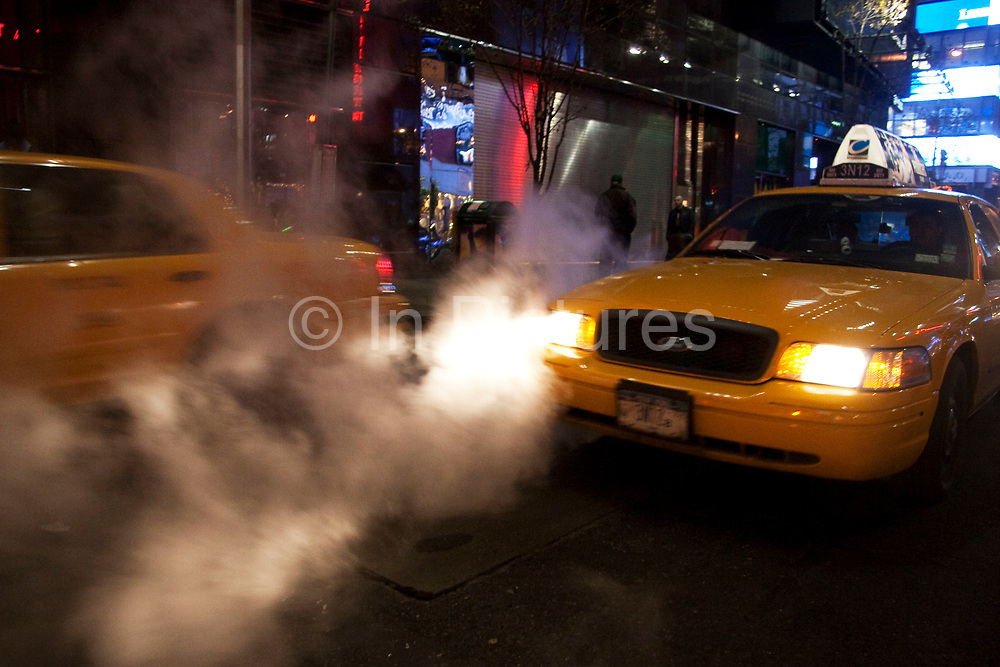 Yellow Taxi cab through steam street scene New York City, USA.