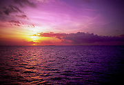 The sky turns purple and orange as the sun sets over the ocean off Tahiti