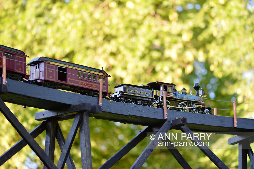 Old Westbury, New York, U.S. June 23, 2021. A Long Island Railroad model train, a large G gauge, travels outdoors on elevated tracks during the Old Westbury Gardens opening reception for its Great Pine Railway exhibit, which runs until September 6.