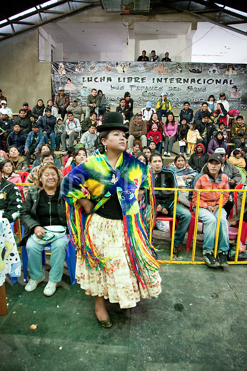 Female wrestler coming out of crowd preparing to fight. Lucha Libre wrestling origniated in Mexico, but is popular in other latin Amercian countries, including in La Paz / El Alto, Bolivia. Male and female fighters participate in the theatrical staged fights to an adoring crowd of locals and foreigners alike.