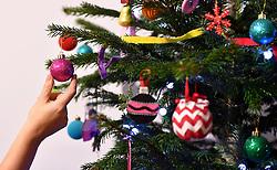 A woman adjusts a decoration on a Christmas tree.