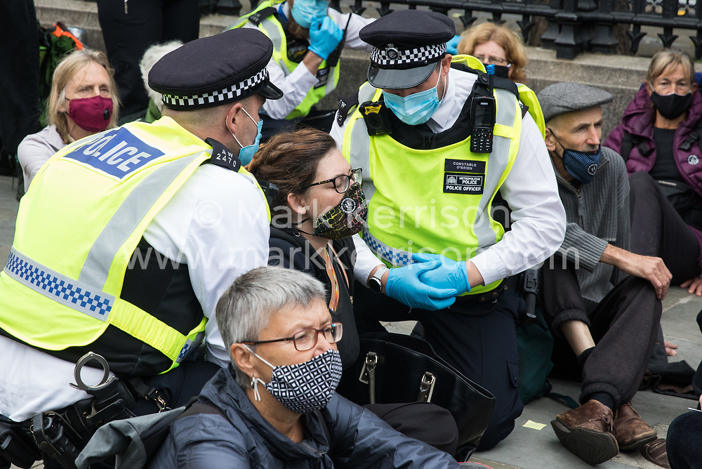 London, UK. 3rd September, 2020. Metropolitan Police officers ask a climate activist from Extinction Rebellion to move from the pavement outside the Houses of Parliament. Extinction Rebellion activists are attending a series of September Rebellion protests around the UK to call on politicians to back the Climate and Ecological Emergency Bill (CEE Bill) which requires, among other measures, a serious plan to deal with the UK's share of emissions and to halt critical rises in global temperatures and for ordinary people to be involved in future environmental planning by means of a Citizens' Assembly.