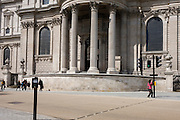 Tourist squats for a picture and pedestrians pass below the pillars and columns of St Paul's Cathedral in Central London.