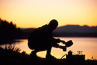 A woman makes backcountry coffee on the shore of Jackson Lake in  Grand Teton National Park, Jackson Hole, Wyoming.