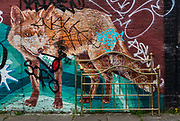 Fox painted on closed Petticoat Lane building with disguarded bedstead during the coronavirus pandemic on the 4th May 2020 in London, United Kingdom.