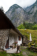 A rock walled house and picnic table are dwarfed by rock cliffs of Zadnjica Valley, a short (3.5km), very-steep-sided offshoot of the Trenta valley which descends directly from Mount Triglav (2864 meters/9396 feet), the highest peak of the Julian Alps, Europe. Mount Triglav is proudly depicted on the Slovenian coat of arms and flag. Triglav is the only National Park in Slovenia (in Slovene: Triglavski narodni park, TNP).