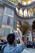 Tourist at Hagia Sophia, Ayasofya Muzesi, mosque museum using Apple Ipad tablet to take photograph in Istanbul, Turkey