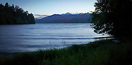 Waves approach the shore during high tide at Holly Bay on the Hood Canal of Puget Sound, with the snowcapped Olympic Mountains in the distance - Washington state, USA