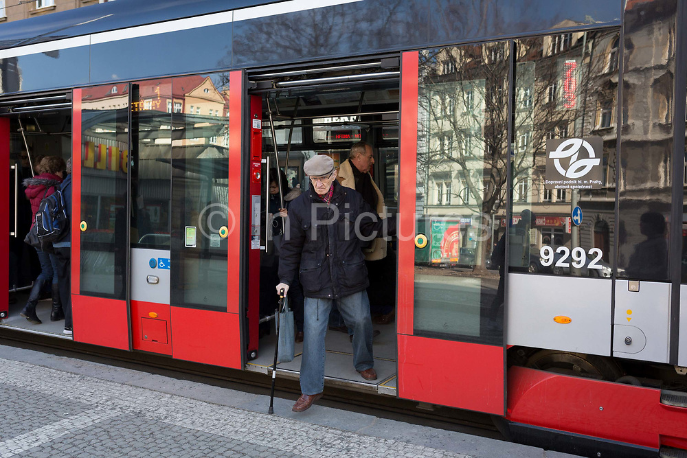 An elderly passenger steps carefully out of a modern tram in the Holesovice district, Prague 7, on 20th March, 2018, in Prague, the Czech Republic.