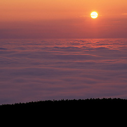 Acadia N.P., ME. The sun rises over a fog enshrouded Frenchman Bay.  From the summit of Cadillac Mountain.