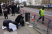 Street cleaner passes praying Islamic extremists opposite London Libyan embassy during the Gaddafi uprising. Holding up their placards that ask for Shariah law for Libya and that Democracy is the path to Hellfire, the young British radicals stand behind barriers near Hyde Park Corner denouncing Colonel Gaddafi and for their views and ideology to become the way of life for the north African country.