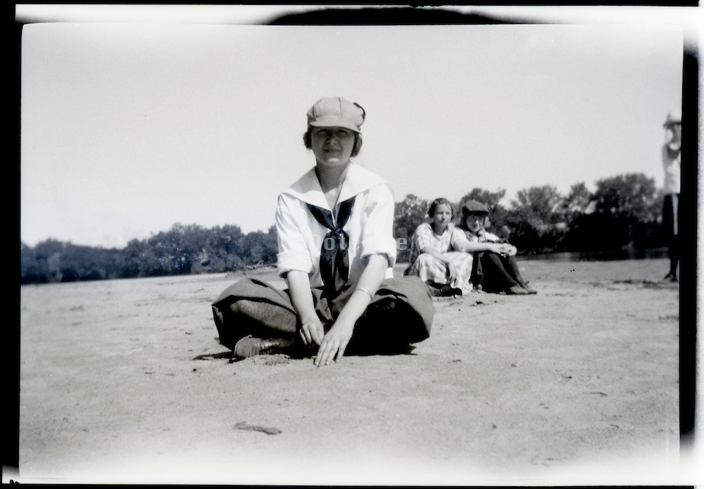 young adult girl sitting cross legged with friends in the background 1920s USA