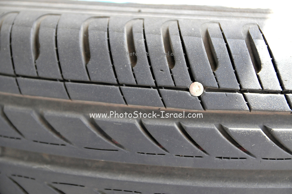 Punctured tyre - a nail embedded in a tyre causing an air leak