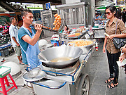 Oct. 9, 2009 -- BANGKOK, THAILAND: A fried pastry vendor does business in front of the Siam Paragon shopping center on the streets of Bangkok, Thailand. Photo by Jack Kurtz / ZUMA Press