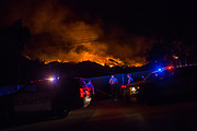 12072017 - Ojai, California USA: Sheriff's deputies watch as fires rage in hills near the city of Ojai, California, where the Thomas fire was threatening the town. One of the deputies said photos don't do the fire justice as he watched. Fire crews were working to burn some of the fuel as the uncontrolled fire approached in a last stand against the fire, which was just outside town, but if the fire would have marched down the slope and through trees, and into the city, it would be hard to stop. The fire was burning from outside Ojai toward the city from two directions. The Thomas Fire, which began Monday, has scorched over 100,000 acres. (Photo by Jeremy Hogan) ©2017 All rights reserved