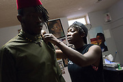 Designer Jacqueline Addison, right, owner of Akua Gabby, secures a tunic on model Moise Damey during a fitting at Addison's studio in Northeast Minneapolis.