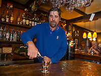 """Ray Simanson pours a glass of scotch in his bar at Tavern 27 to promote the """"Exquisite Scotch Flight"""" an upcoming event later this month.  (Karen Bobotas/for the Laconia Daily Sun)"""