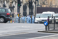 Scotland Yard, London, March 23rd 2017. Police in forensic suits are briefed outside Parliament in the aftermath of Tuesday's terrorist attack on Westminster Bridge and in the grounds of Parliament, in which four people and their attacker were killed with over 40 injured.