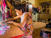 24 FEBRUARY 2015 - PHNOM PENH, CAMBODIA: A resident of the White Building does sewing work in her apartment. The White Building, the first modern apartment building in Phnom Penh, originally had 468 apartments, and was opened the early 1960s. The project was overseen by Vann Molyvann, the first Cambodian architect educated in France. The building was abandoned during the Khmer Rouge occupation. After the Khmer Rouge were expelled from Phnom Penh in 1979, artists and dancers moved into the White Building. Now about 2,500 people, mostly urban and working poor, live in the building. Ownership of the building is in dispute. No single entity owns the building, some units are owned by their occupants, others units are owned by companies who lease out apartments. Many of the original apartments have been subdivided since the building opened and serve as homes to two or three families. The building has not been renovated since the early 1970s and is in disrepair. Phnom Penh officials have tried to evict the tenants and demolish the building but residents refuse to move out.   PHOTO BY JACK KURTZ
