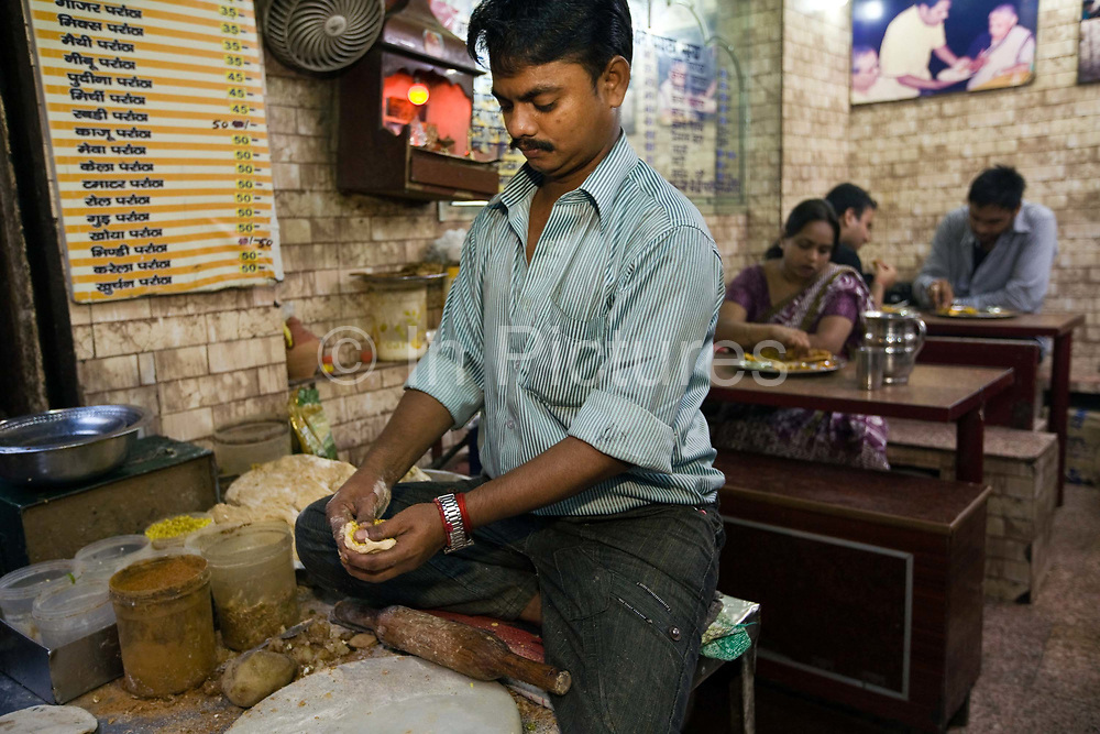 Ram Billas making paratha at Parawthe Wala restaurant in Old Delhi, India<br /> The parantha is an Indian fried bread, folded and filled with fillings and then fried.<br /> Gali Paranthe Wali or Paranthe wali Gali means the the street of fried bread and name of a narrow street in Chandni Chowk Old Delhi, noted for its series of shops selling paratha