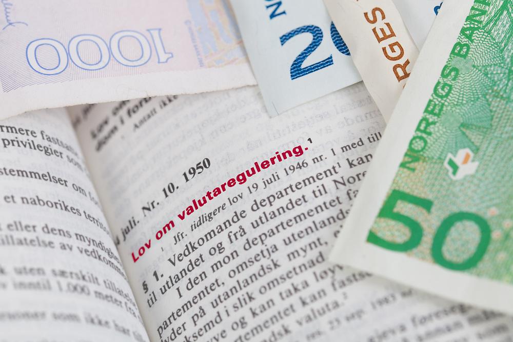 Fokus på innledningen til «lov om valutaregulering» i Norges lover. Sedler understreker tematikken. Tittelen er uthevet i rødt.