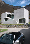 villa design in concrete, external view with luxury car