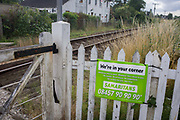 A Samaritans sign lending emotional support and safety for those considering suicide at an unmanned level crossing in Reedham on the Norfolk Broads. Isolated railway lines like this in the UK are often locations where the desperate make serious decisions about their lives and the Samaritans make their presence known by placing signs with their phone numbers as a deterrent in this rural corner of Britain known as East Anglia, known for its flat fenland landscape, wide skies and small communities.