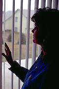 Silhouette of a woman age 28 looking out her window.  St Paul  Minnesota USA